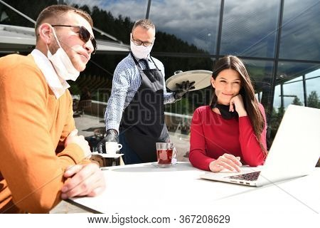 coronavirus outbreak Group of casual business People in outdoor restaurant wearing protective medical mask, business team collaborating and brainstorming business ideas  while working on laptop