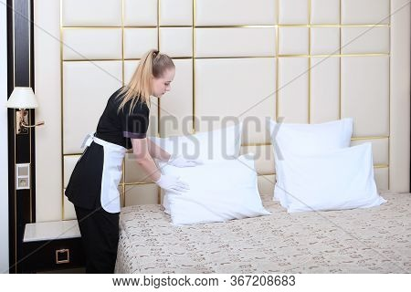 A Maid In An Expensive Hotel Adjusts The Pillows In The Bedroom. Hotel Room Cleaning. Copy Of The Sp