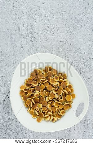 Pancake Cereal. Trendy Food, Mini Cereal Pancakes In Bowl On The Table, Cement Vertical Background.