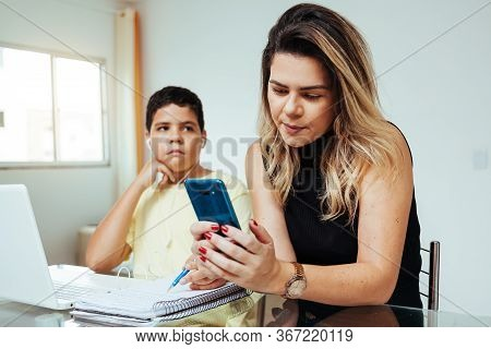 Mother Using Cell Phone Ignoring Her Son While He Is Doing Homework. Concept Of Home Education In Qu