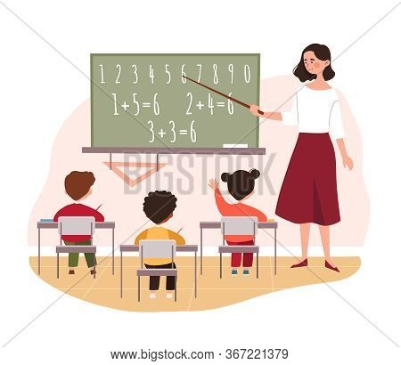 Teacher Teaching Primary School Children In Class Pointing To A Blackboard With Simple Arithmetic, C