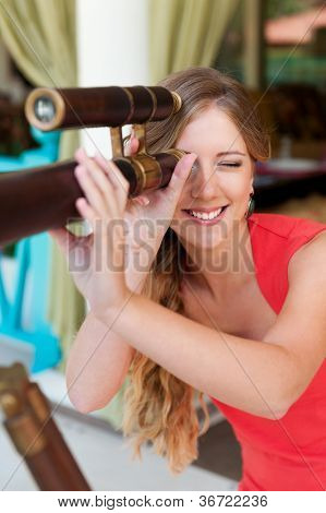 young smiley woman looking through the telescope