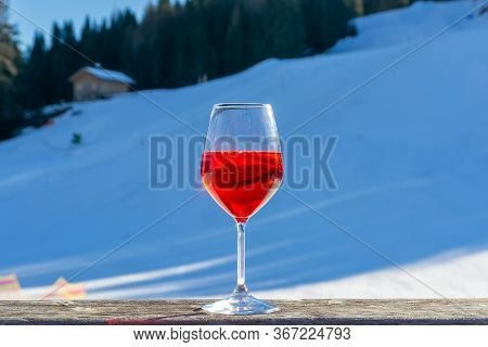 The Glass Of Aperitif On Wooden Table Over Winter Landscape