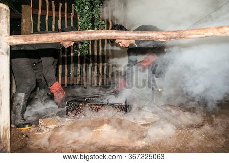 Rotorua New Zealand - April 23 2014; Smoke And Dust Fly As Food Is Being Prepared For A Traditional