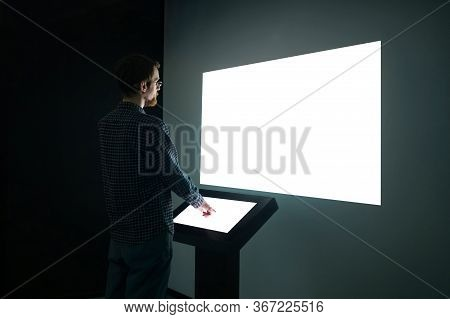 Man Using Electronic Kiosk And Looking At White Blank Large Interactive Wall Display In Dark Room Of