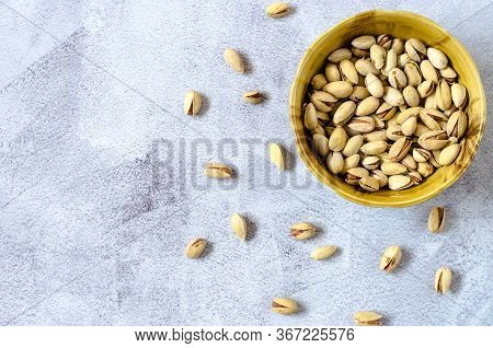 Pistachios In A Brown Bowl. Pistachios On A Light Background. Top View, Flat Lay.