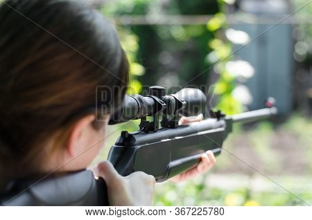 Girl Sniper Holds A Gun In His Hands. The Hunter Is Looking Into The Optical Sight From A Rear View.