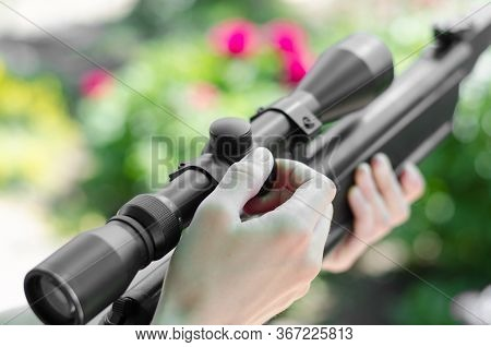 Man Sets Up The Rifle Scope. Preparing Weapons For Shooting. Woman With Guns