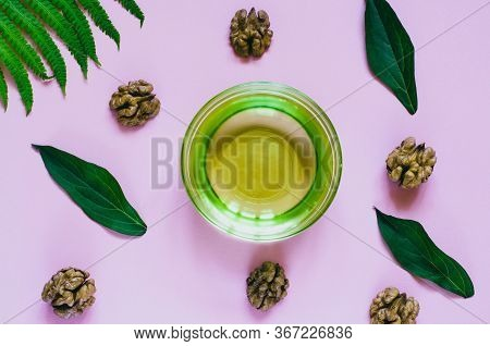 Walnut, Bowl With Walnut Oil, Green Leaves And Fern Leaf On A Pink Background. Natural Organic Produ