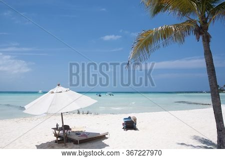 Blue Sky Caribbean Beach With Palms And Umbrella. White Beach In Isla Mujeres, Mexico, America.