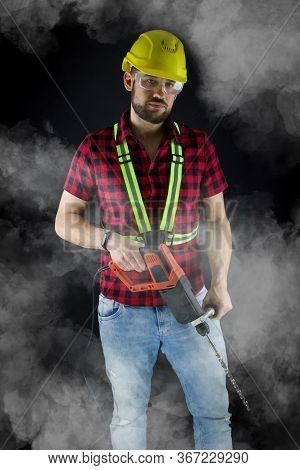Construction Worker With A Large Demolition Hammer  On Black Background.construction Worker With Yel