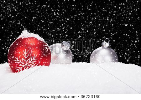 red and silver christmas balls in snow