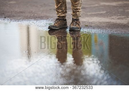 A Man In Sneakers In Puddles With A Reflection