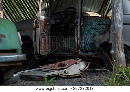 An Old Rusty Abandoned Car With Its Doors Open