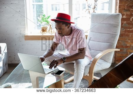 African-american Musician Typing Text With Laptop Sitting At Home, Musician During Quarantine. Using