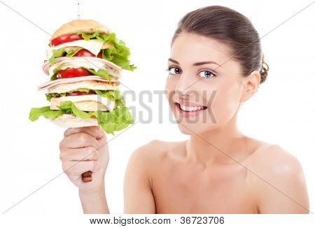 Young  woman holding a big sandwich on a spike and smiling at the camera, on white background.