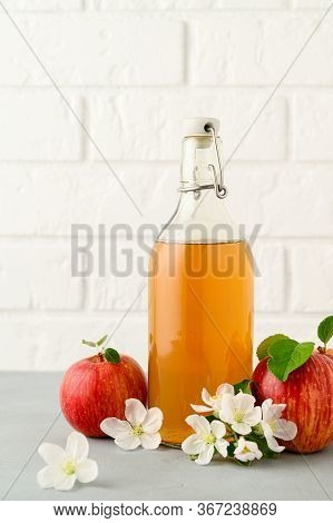 Homemade Fermented Kombucha Or Cider Drink In A Glass Bottle And Apples On A Light Gray Stone Table.
