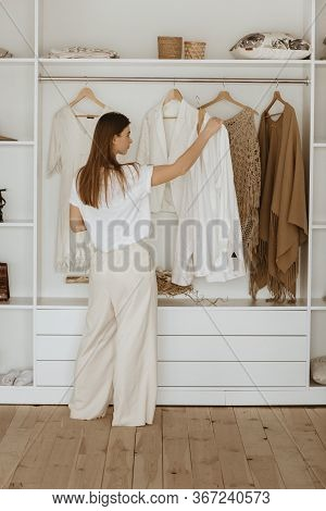 Young Woman Standing In Front Of Her Closet And Deciding What To Wear.