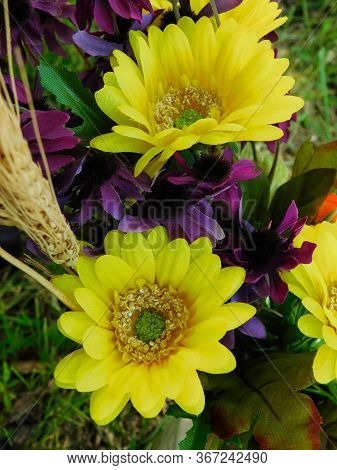 Faux Yellow And Purple Silk Flowers Line The Aisle At An Outdoor Wedding