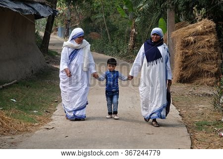CHUNAKHALI, INDIA - FEBRUARY 26, 2020: Missionaries of Charity - Mother Teresa nuns walk with child in Chunakhali, West Bengal, India