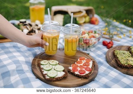 Woman Take Fresh Orange Juice On Vegan Picnic Outdoors, Picnic On Blue Checkered Blanket In Park. Ve