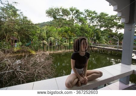 Mixed-race asian girl sits on the terrace of the Bungalow.