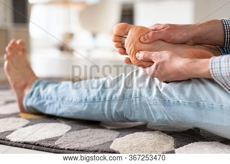 Man Hands Giving Foot Massage To Yourself To Relieve Pain After A Long Walk, Due To Uncomfortable Sh