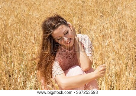 Beautiful Teenage Model Girl Lying On The Field In Sun Light. Late Summer. Beauty Romantic Girl Outd