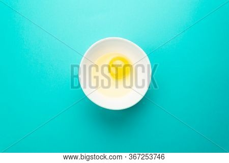Raw Egg In Bowl On Blue Background. Healthy Food And Cooking At Home Concept.