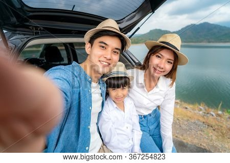 Portrait Of Asian Family Sitting In Car With Father, Mother And Daughter Selfie With Lake And Mounta