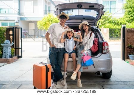 Portrait Of Asian Family With Father, Mother And Daughter Looks Happy While Preparing Suitcase Into