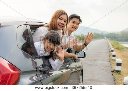 Happy Asian Family With Father, Mother And Daughter In Compact Car Are Smiling And Bye Bye When Driv