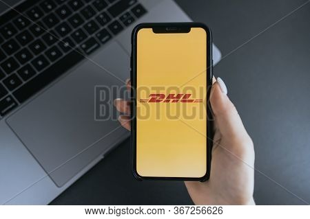 Hand Holding Iphone X With Dhl Logo On The Screen. Dhl Is A Popular Delivery Company.