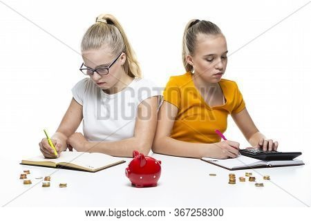 Kids Financial Ideas. Caucasian Teenager Twin Girls Posing With Coins And Piggy Bank. Storing Up Mon
