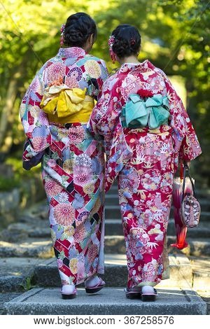 Japan Destination. Two Young Female Geishas In Traditional Japanese Floral Silk Kimono Going Uphill