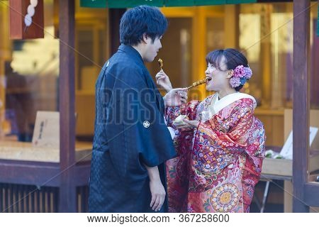Kyoto, Japan - November, 8, 2019: Young Lovely Couple In Traditional Geisha Kimono Feeding Each Othe