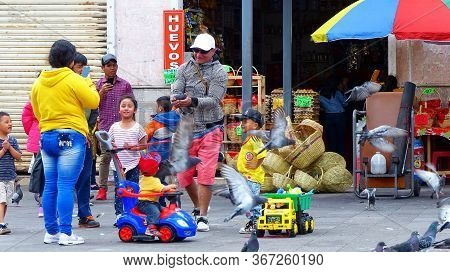 Cuenca, Ecuador - December 23, 2018: Family With Little Children Have Fun Playing With Pigeons At Pl