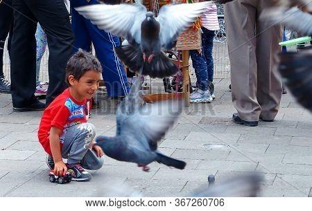 Cuenca, Ecuador - December 23, 2018: Boy Of 5-6 Years Old Have Fun Playing With Pigeons. Cuenca. Ecu