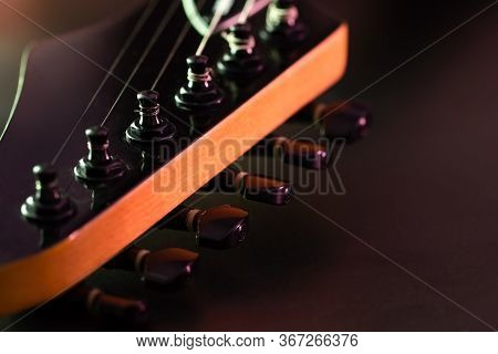 Closeup Tuning Key On The Headstock Of The Black Electric Guitar In Dark Background And Morning Ligh