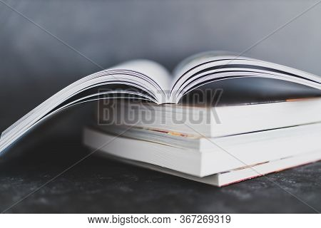 Stack Of Books With One Open On Top Of Themshot From Eye Level With Shallow Depth Of Field
