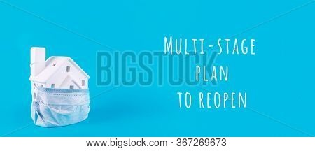 Cute Little House Covered With Medicine Mask On Blue With Multistage Plan To Reopen Wording. Coronav