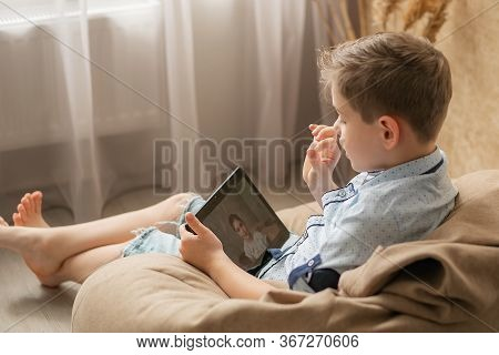 The Boy Communicates With His Girlfriend Online. The Girl On The Screen Of The Tablet Smiles And Lis