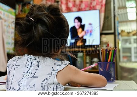 Close Up Schoolgirl Learning Online Sitting On Floor And Watching Television To Learning Online Cour