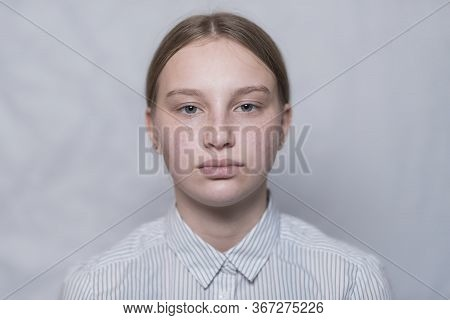 Portrait Of A Teenage Girl 15 Years Old, White Uniform Background, Striped Shirt. Freckles On The Fa