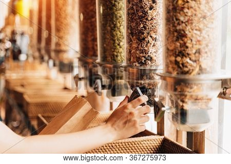 Woman Buying Cereals And Grains In Sustainable Plastic Free Grocery Shop. Dispensers For Cereals, Nu