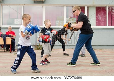 Komsomolsk-on-amur, Russia - July 21, 2018. Kickboxing Coach Will Practice Punch With Boy Outdoor In