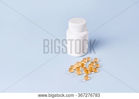 Omega 3 Fish Oil Capsules Spilling Out Of White Plastic Bottle On A Blue Background.