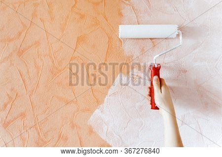 Woman Hand Painting A White Color With A Paint Roller On Orange Wall. Self-made Repair At Home Durin