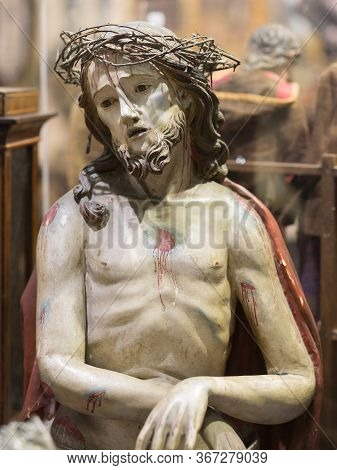 Parma, Italy - October 2019: Small Statuette Of Jesus Christ With Crown Of Thorns And Blood On The B