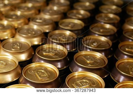 Many Aluminum Cans Stand In A Row On A Shelf Close-up. Tops Of Aluminum Cans Closeup In A Row On A R